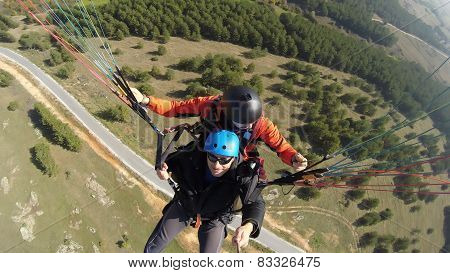 Two man paragliding above mountain