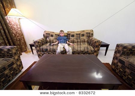Little Boy With Remote Control Sitting At Brown Sofa In Room With White Walls And Watching Tv Genera