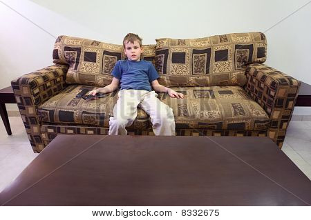 Little Boy With Remote Control Sitting At Brown Sofa In Room With White Walls And Watching Tv