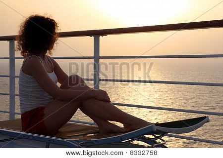 Girl Sitting On Beach Chair At Ship Deck And Looking Into The Di