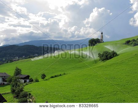 Ridge On Alpine Pasture With Grass Sprinklers