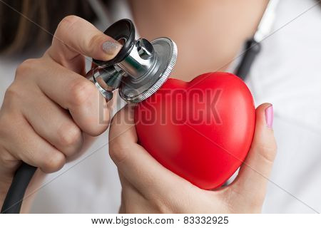 Female Doctor With Stethoscope Listening To The Heartbeat