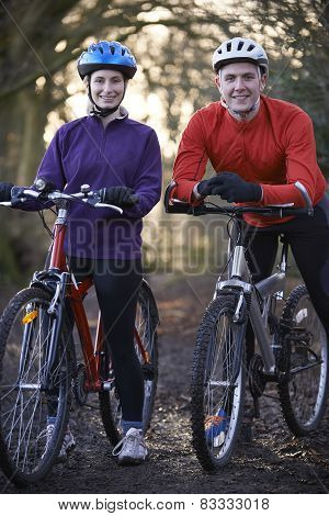 Couple Riding Mountain Bikes Through Woodlands