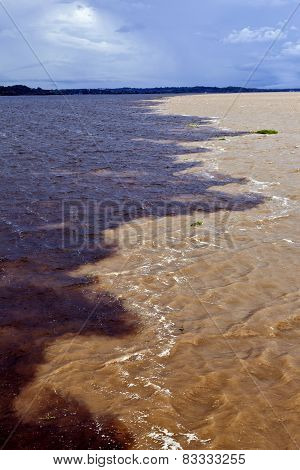 Meeting of the rivers, sandy colored Rio Solimoes and dark Rio Negro, in Brazilian Amazon on a thund