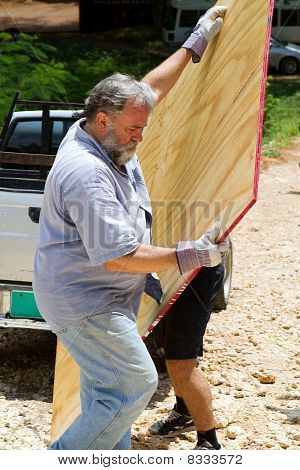 Man Unloading Plywood