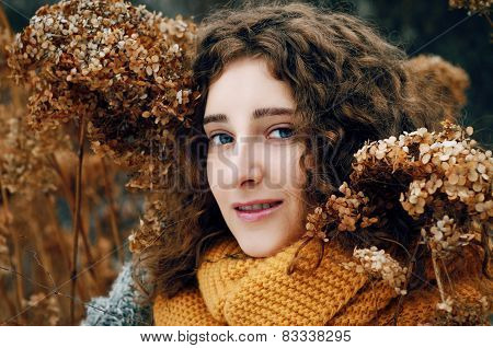 Attractive Young Woman With Curly Hair Near Dried Hydrangea Flowers