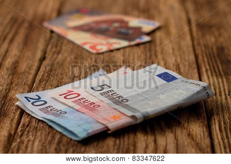 Euro Bills On Wooden Board With Credit Cards In Background