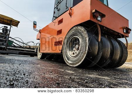 Pavement machine laying fresh asphalt or bitumen on top of the gravel base during highway construction