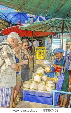 BANGKOK, THAILAND, DECEMBER 26, 2013: Tourists family buys coconuts to drink from street seller