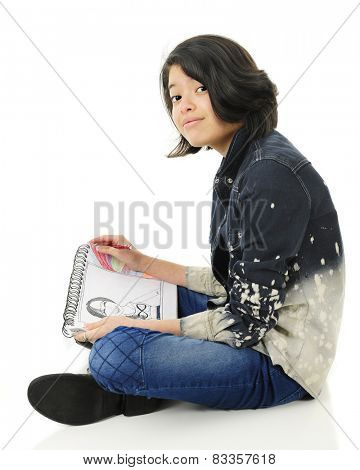 A pretty young teen sitting on the floor looking up at the viewer from her sketching.  On a white background.
