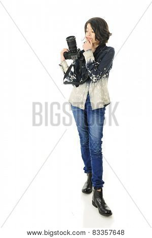 A pretty young teen wondering what to take next with her pro camera.  On a white background.