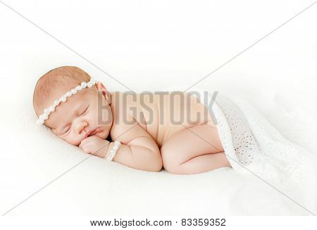 Photo of a newborn baby curled up sleeping on a blanket