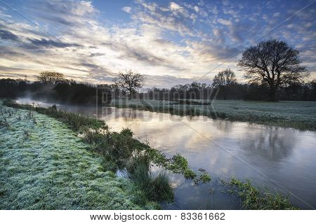 Countryside Sunrise Landscape With Moody Sky And Flowing River
