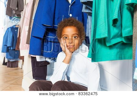 African boy with hand on cheek bored in shop