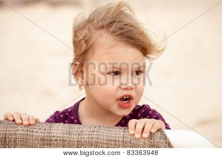 Portrait Of Cute Blond Baby Girl With Wind In Her Hair