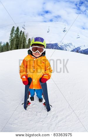 Cute boy wearing ski mask and helmet stands