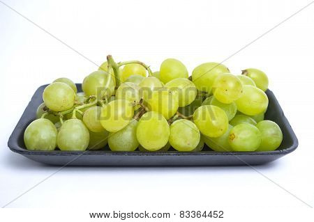 a bunch of green grape on black styrofoam with isolated white background