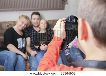 A boy taking picture of his family