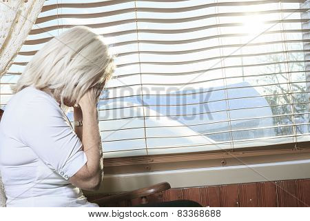 A senior portrait of a woman having a headache