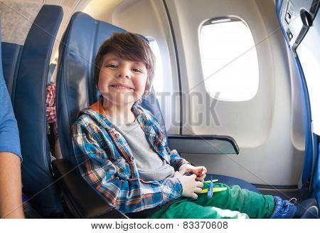 Portrait of little boy in airplane seat by window
