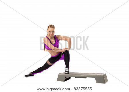 Grinning girl doing shaping exercise on stepper