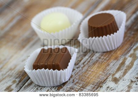 Assorted chocolates on wooden surface