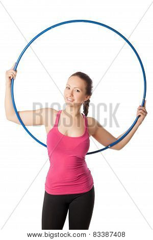 Closeup of young woman standing with hula hoop up and back