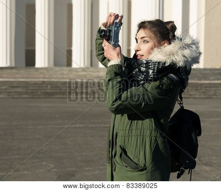 The girl in the green jacket photographs vintage camera outdoors on a sunny spring day