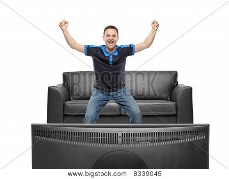 A view of a happy sport fan watching TV
