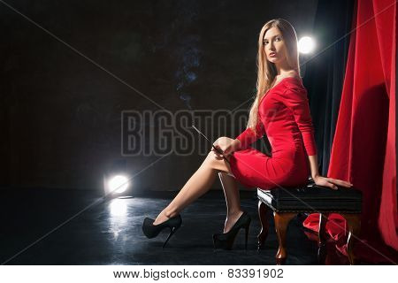 Glamorous young woman with cigarette sitting on stool  .