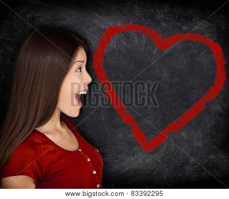 Heart love woman portrait on blackboard chalkboard background. Surprised Asian woman at heart shape drawing showing St-Valentines day concept.