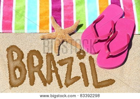 Brazil concept. Overhead view ot the word BRAZIL written on beach sand with a colorful striped towel, pink thongs and a starfish conceptual of a summer vacation and travel in Rio de Janiero, Brazil.