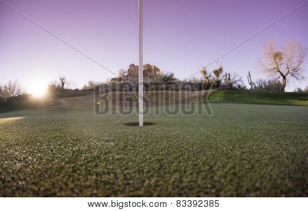 Extreme wide angle viewpoint of putting green hole and flag with sun setting over mountains. Arizona,USA