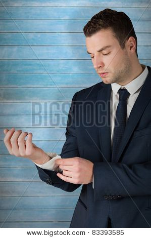 Businessman adjusting his cuffs on shirt against wooden planks