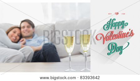 Couple resting on a couch with flutes of champagne against valentines day greeting