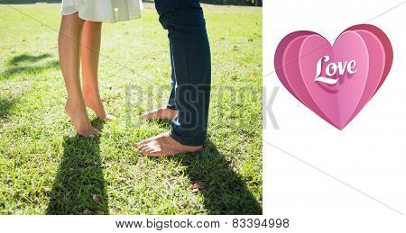 Couples bare feet standing on grass against love heart