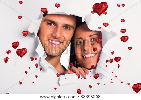 Young couple looking through paper rip against red heart balloons floating