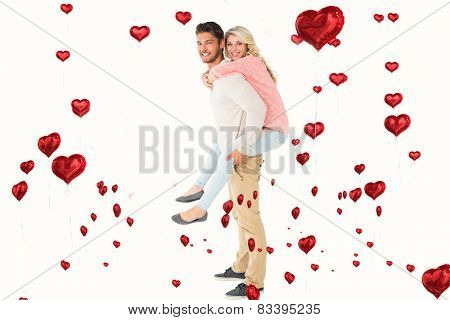 Handsome man giving piggy back to his girlfriend against red heart balloons floating