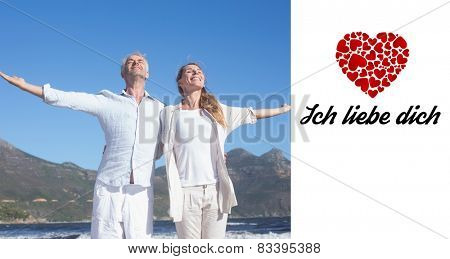 Happy couple standing with arms outstretched at the beach against ich liebe dich