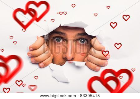 Young man looking through paper rip against hearts