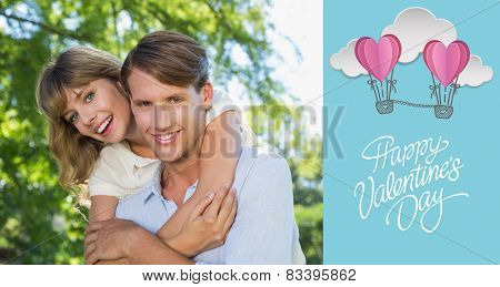 Man giving his pretty girlfriend a piggy back in the park smiling at camera against cute valentines message