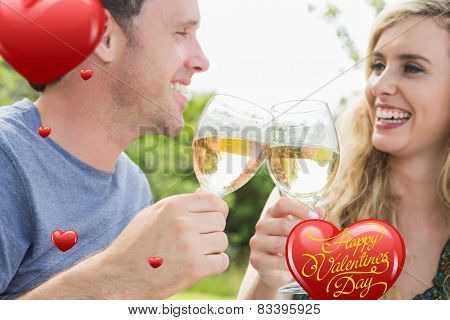 Cheerful couple toasting with white wine against happy valentines day
