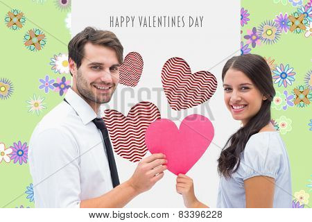 Pretty brunette giving boyfriend her heart against digitally generated girly floral design