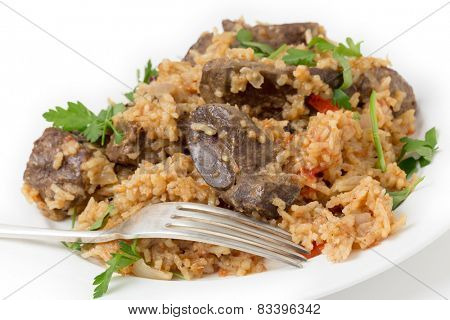 lightly fried lambs liver chunks baked on top of a pilaf of rice, onion, tomato, capsicum and dried currants in a chicken broth, on a small plate garnished with flat-leaf italian parsley.