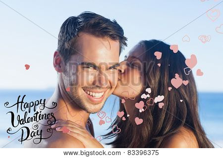 Attractive woman kissing her boyfriend on the cheek against happy valentines day