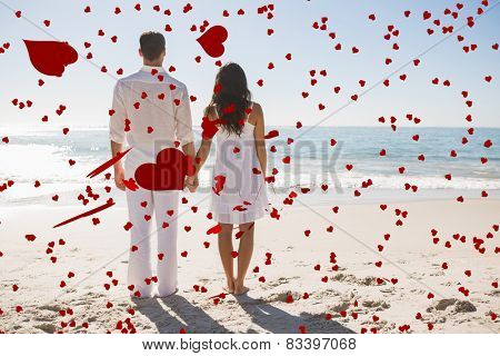 Attractive couple holding hands and watching the waves against love heart pattern
