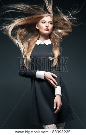 Closeup portrait of blond model posing with hair fluttering in the wind