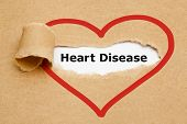 stock photo of hypertensive  - The text Heart Disease appearing behind torn brown paper - JPG