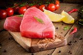 picture of flank steak  - Raw tuna fillet with dill lemon and cherry tomatoes in olive cutting board - JPG