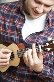image of ukulele  - Close Up Of Smiling Man Playing Ukulele - JPG